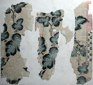 Irregular fragments of paper with ground originally pink, printed with large-scale vine pattern in black, blue-grey and white. Portion of geometric border attached to fragment.