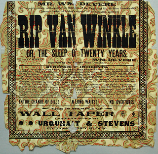 """On a fleur-de-lys rococo or Aesthetic-style wallpaper fragment, pattern by Urquhart & Stevens Wallpaper Co. Printed with an advertisement for a presentation of """"Rip van Winkle,"""" a dramatization by Dion Boucicault. It also advertises the wallpaper product by the manufacturers."""