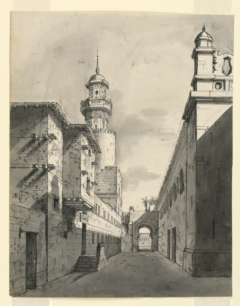 Vertical rectangle. Street in town with rows of buildings on either side, tower at left.