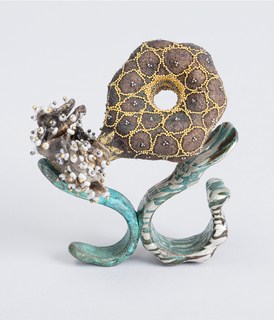 Mushroom-like form made in designers pulverization technique of silver to be a bronze color applied with gold beads, and inside depression with rows of yellow and white gold beads, emerging from a pearl- and-gold--studded petaled form,  emerging from the Shibuichi -created S-form ring in bright copper color, which is attaced to the green and silver patterned, mokumegane larger ring