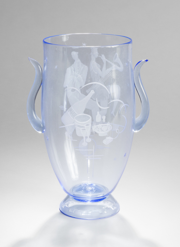 Of ovoid vase form, with two bull's-horn shaped handles, the slightly powdery blue glass, deep engraved with fanciful figures dancing and playing a horn-form instrument with 18th-century hair styles, surrounded by stars and an engraved orb with cross-cut lines; the opposite side engraved with an outdoor picnic scene with bursting Champagne bottle and bubbles with bowl of fruit and wine glasses, all resting on an inverted conical  foot engraved with stepped decoration