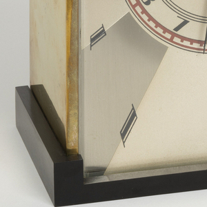 Rectangular clock with geometric surface pattern on face in alternating light and dark brasslike metalic tones punctuated by black lozenges; circular dial in center with stylized arabic numerals within red border; two-toned, tapered metal hands; black Bakelite base and back with central opening for setting dials.