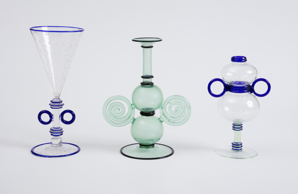 "Part of the ""Trasparente"" series. The double bubble body is made of clear, colorless glass layered with air bubbles that form a regular pattern. The body of the vessel rests on a stem made of greenish, transparent glass.  The narrow lip of the vessel is rimmed in cobalt blue, as is the waist of the vessel, and the circular foot. Decorative cobalt blue glass disk decorate the stem; circular handles, also made of cobalt blue glass, are attached to the vessel at the waist."
