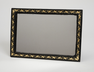 Rectangular mirror (-1d) within black leather frame with gilded foliate decoration; back covered in black leather. Part of a travelling case (-1a: case;  -1b: jewelry drawer; -1c: jewelry drawer cover; -1d: mirror; -1e: interior tray with silver handles; -1f: tray for manicure tools; -1g: key) that houses a traveling dressing set comprising: rectangular case ,lined with purple silk, fitted with leather document holders, and mirror with gold-leaf foliate border, the upper level withy 4 rectangular and 1 central faceted silver-lidded cylindrical cologne jars, 3 silver-lidded glass boxes, 2 silver-lidded glass ink bottles, mother-of-pearl handled sewing implements, tweezers, button hook, pen knife and hole punch or scorer-all in the upper compartment, a secret drawer below fitted with a letter writing slide.