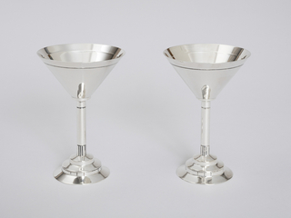 Two cocktail cups. The cup is in the shape of a cone, and is ornamented with a simple line near the rim. The stem is of approximately the same height as the cup and is attached to a base made of three stepped concentric circles.