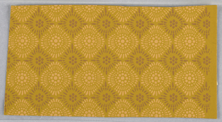 Alternating, stylized pattern of sunburst in brown and pink on mustard ground. One selvedge.