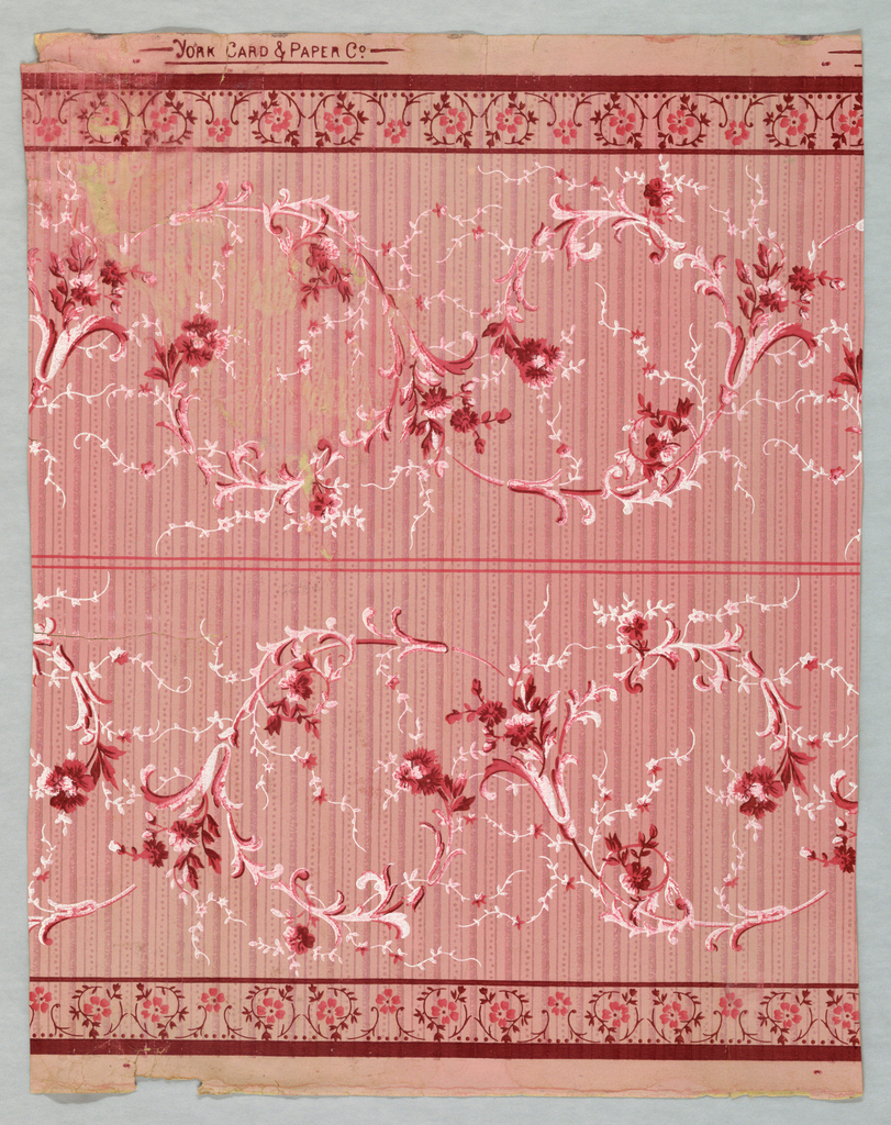 Matching sidewall and border. Wallpaper contains floral bouquets and scrolling foliate scrolls.Printed in red and white on mica-striped background. Maroon, rose and white floral scrollwork on pink ground. Border is printed two across the width. Floral bouquets and scrolling foliate sprigs, narrow band of scrolling florall and foliate motif at bottom edge. Printed in red and white on pink striped background.