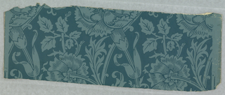 A repetitive pattern with a variety of flowers including carnations and stylized flowers with Persian accents. Printed in light blue design on dark blue field.