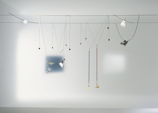 "Ingo Maurer's most influential and most highly-copied design is his 1843 the low-voltage ""Ya-Ya Ho"" system, in which halogen lamps are combined with different shape shades, materials, and reflective components, and hung like jewelry on cables that strech wall to wall."