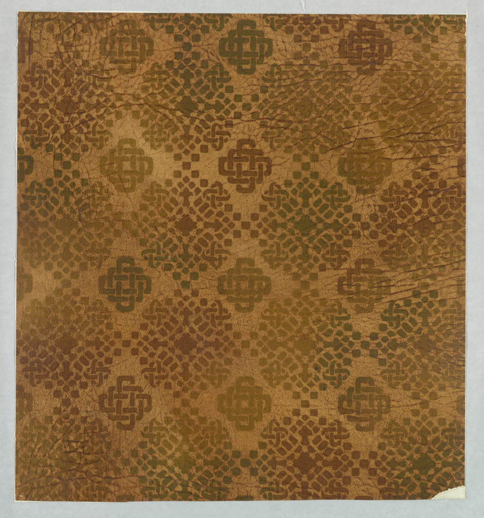 Medium sized diamond shaped motifs of geometric design of small broken lines in greens and browns. Between are smaller diamond shaped motifs of interlaced geometric borders also in greens and browns on tan field. Field is embossed to simulate grained leather. Entire paper is antiqued by hand. The effect is that of stencil work.