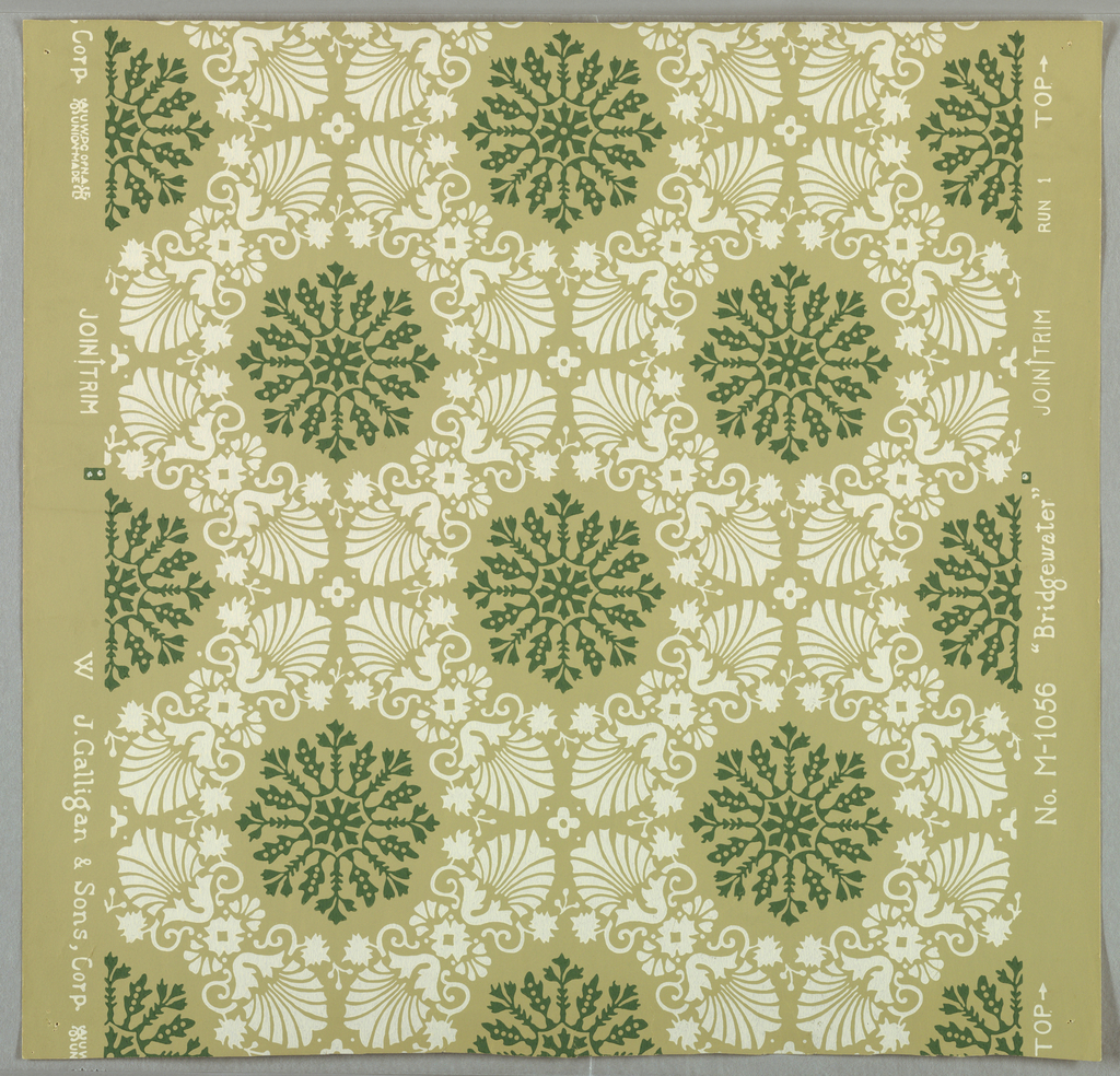 Framework of white palmettes and flowerlets encloses a wheel-shaped medallion of green sprigs and leaves. Drop-repeating arrangement. Straight across match. Printed on tan ground.