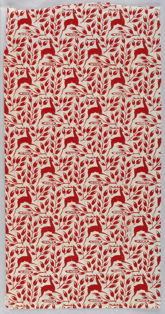 Red pattern on a white ground showing reindeer surrounded by leaves.