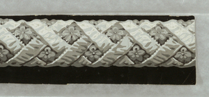 Open-weave rope border, with stylized floral motif in space between ribbons. Printed in grisaille. Similar in nature to rope twist or cable molding borders.