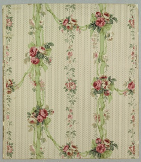 Full width, giving more than one repeat of design. Vertical arrangement of green ribbons, with swags of intertwined green ribbons, set with clusters of flowers. Secondary vertical arrangement of slender vine with flowers. Striped and dotted ground. Printed in pinks, greens and grays on white ground.