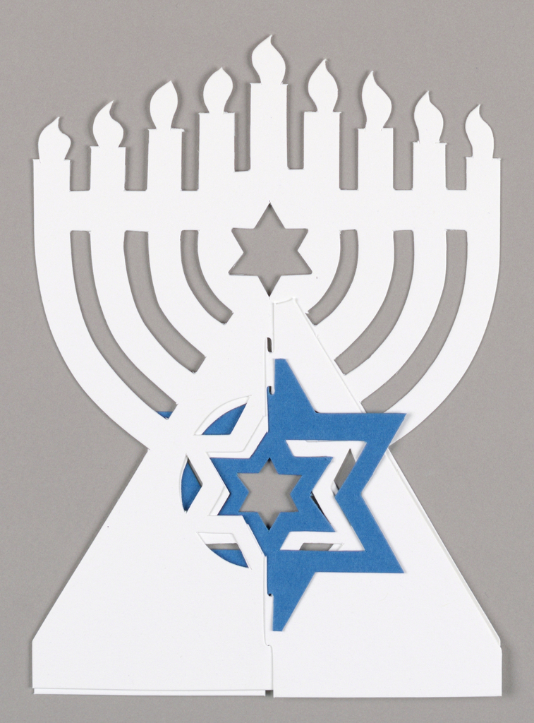 Greeting card for the Jewish holiday of Hanukkah. Features a white menorah with nine candles and a six-pointed Star of David cut out of the center. Below, on the triangular-shaped base, a larger, blue and white Star of David appears in the center.