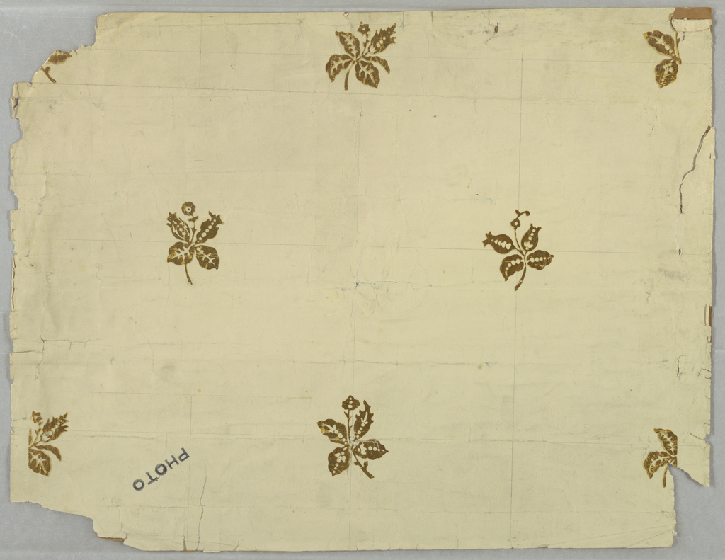 Stylized floral sprig, in metallic gold, printed on a creamy, off-white ground.