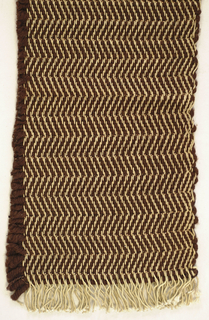 Upholstery fabric with a natural cotton warp and thick brown wool weft with a small amount of copper Lurex and cotton chenille, in a herringbone twill pattern.