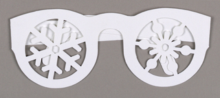 Greeting card cut in the shape of eyeglasses with snowflake patterns cut-out where lenses would be.