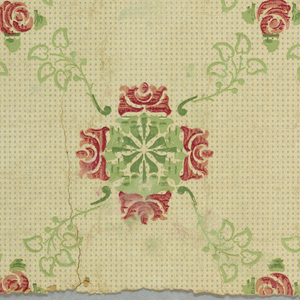 Small red roses, connected by green foliage, alternating with clumps of four roses. Printed on off-white ground spotted with tiny gray squares.