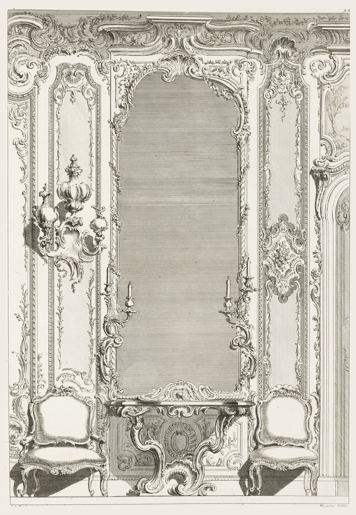 Elaborate boiserie decoration with tall pier mirror as central focus, rococo console table with shell motif below. Candelabra flank mirror, wall bracket with arrangement of two ewers and one covered vase (at left). Louis XV arm chair at left, side chair at right.