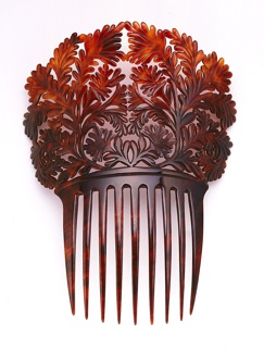 Ornamental tortoiseshell comb with large decorative panel carved as scrolling leaves above long teeth.