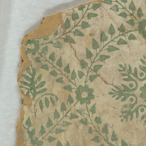 Two pieces mounted on corrugated cardboard. Foliate framework composing network of circles and squares. The point of intersection is covered by a floral motif. The circular framework contains a floral, snowflake or crystalline motif. The square framework contains a plant motif. Printed in green on white ground.