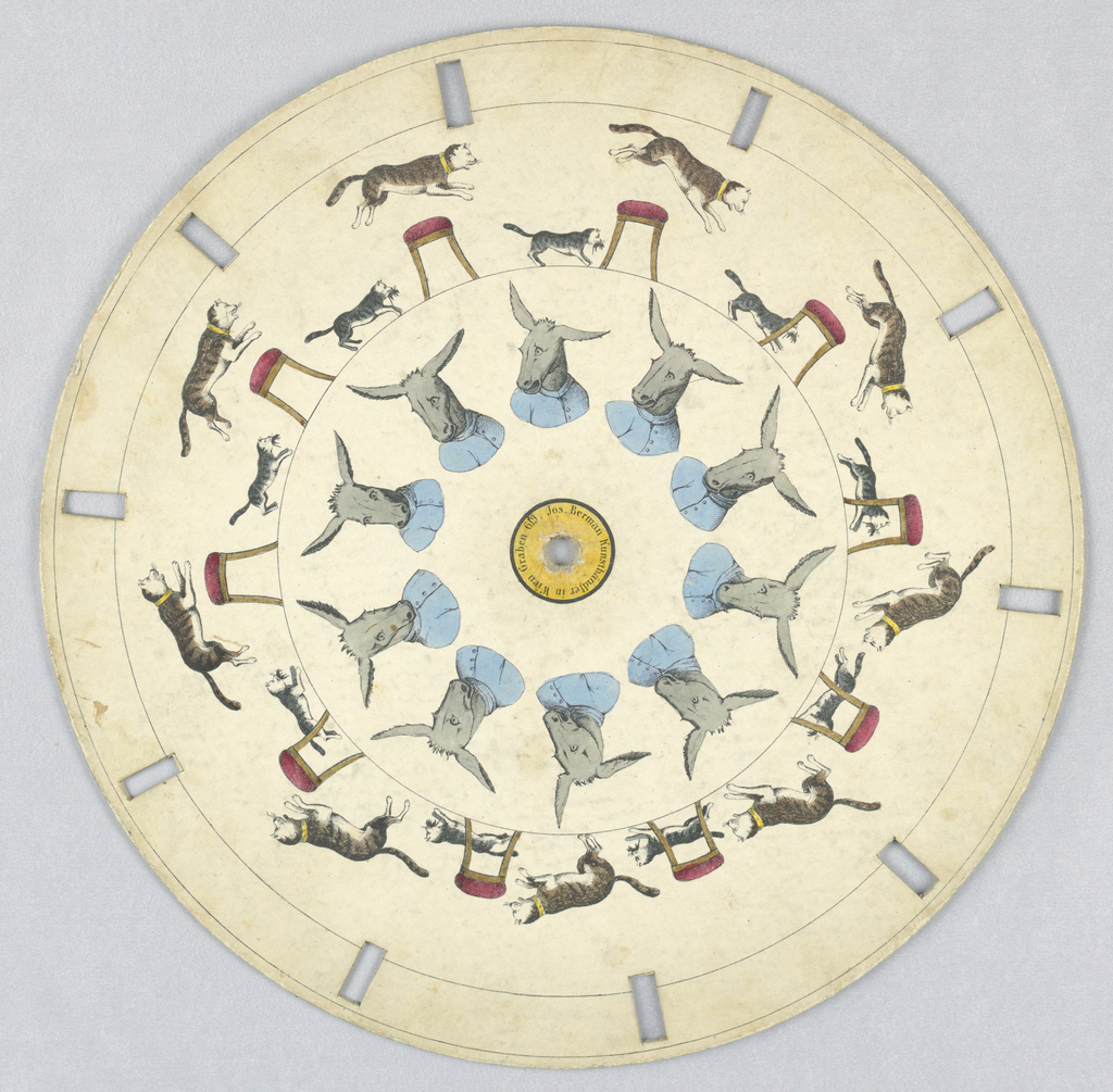 Paper disc with a hole in the center, 10 rectangular perforations evenly spaced along perimeter for viewing. In the outermost ring, several still images show the progress of a large cat chasing a small cat with a mouse in its teeth; the large cat jumps over a stool with a red cushion. In the innermost ring, a donkey wearing a blue shirt moves its ears.