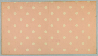 Design of white dots on pale pink ground.