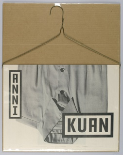 "Newsprint publication folded over wire hanger. The ensemble shrink-wrapped against corrugated cardboard backing so it could be sent directly through the mail. Cover of brochure, photographic reproduction of button down shirt (shown in inverse).  Imprinted vertically along top left edge, ""ANNI"" (in black) inside black oulined text box.  Imprinted at bottom right, ""KUAN"" (in black) inside black outlined text box (larger font).  One interior page shows photographic reproduction of strips of fabric used to construct information about event, ""ANNI KUAN AT/ PIERS ON THE HUDSON FASHION/ 55 ST & 12 AVE. COTERIE/ NEW YORK/ FEB. 21 1999/-FEB. 23 CITY"". Rest of pages are inaccessible because clear plastic seal around entire brochure."