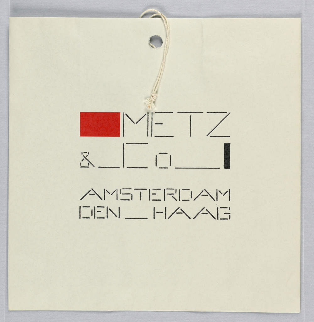 White square bag with a De Stijl logo in black and red ink. The logo starts off with a red rectangle followed by the words METZ__&__Co in black ink. These words are terminated by a black rectangle. On the second line the word AMSTERDAM and on a third line, DEN__HAAG. The letters are made up of thin dashes and lines with small separations. There is a hole punched at the top center of the bag and string is attached to the bag.