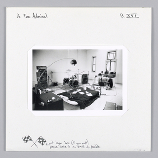 Photograph of a recording studio with equipment and a bed. Text in black ink, upper left: A. The Admiral; upper right: B. XVI; lower margin: [two flags] put logo here (if you must) / please make it as small as possible.