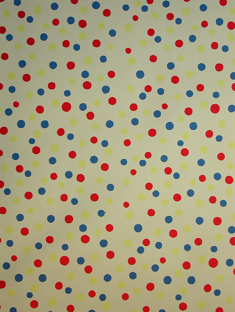 Pattern of closely spaced polka dots printed in red, yellow and blue on a light yellow ground.