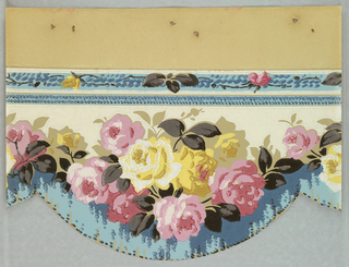 Pink and yellow roses above bullion fringe with scalloped bottom edge. Band of ribbon and flowers across top.