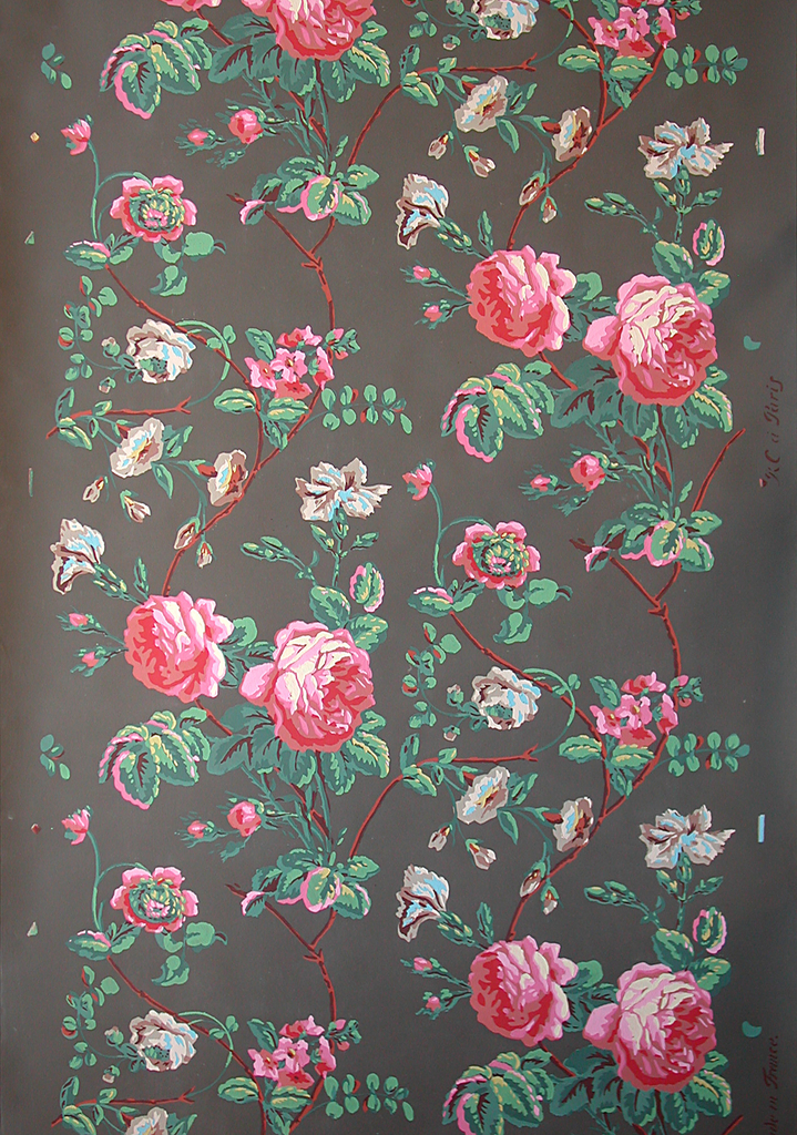 Vining floral design. Based on a c. 1800 paper it contains large red roses and other flowers. This design repeats twice across the width. This is a reproduction of CHM 1972-42-189. Printed in colors on a deep brown ground.