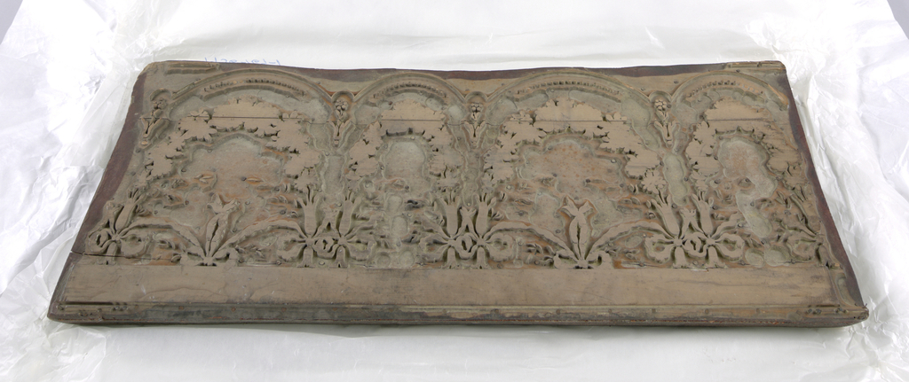 Rectangular block of five layers of laminated wood, of which the upper one is carved. Straight top, two large and two small scallops at bottom, fitted with summarily indicated swags and bows. First block of a set of three (1956-164-2 and -3).