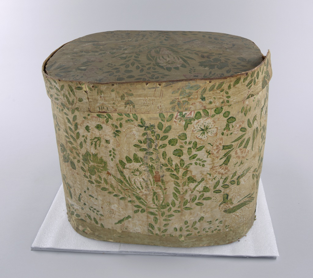"""Yellow background, pink and deep bright pink flowers with touches of white, green leaves: carnations, butterflies, birds, roses in fairly random scattered pattern. Paper on exterior much faded: background appears to be beige with brown and green pattern. Just inside rim, well-preserved, brightly colored pieces. Printed paper label inside lid on yellow paper: """"Warranted Nailed/Band Boxes/ Manufactured by/Hannah Davis/ East Jaffrey, NH"""""""