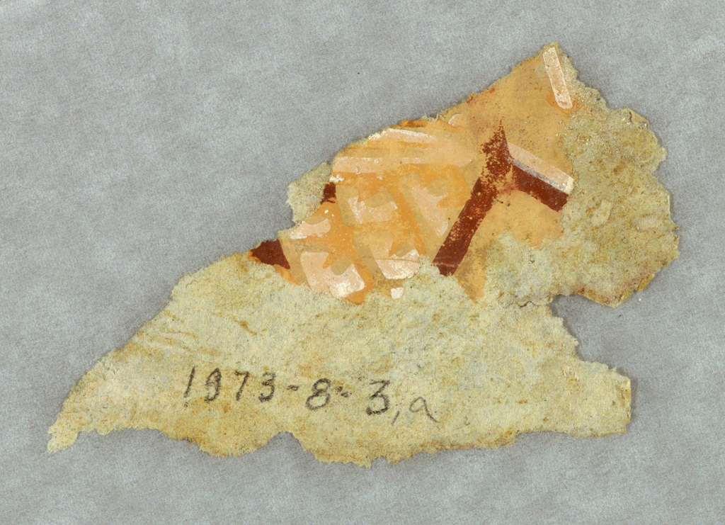 """Very small fragments. a) rag paper, a very small portion of which contains any pigment. The design appears to be printed in deep rust, white and a salmon-color on a lighter salmon-color ground. The rust-color forms a """"Y""""-shaped motif. The verso contains fine yellow line markings along one edge; b) This appears to be a ribbon wrapped rod. It is printed in red on deep red flock."""