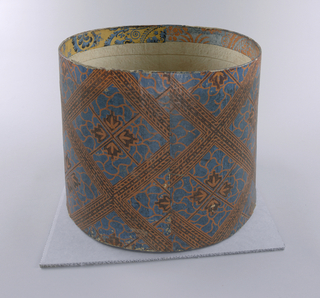 Tall cardboard bandbox covered in wallpaper of geometrical salmon and blue pattern, with brown. Squared, large diamond shapes with seaweed-like fill and symmetrical flower or leaf forms. Inside rim, fragments of two different wallpaper patterns, one salmon on light blue, one blue on yellow. Two wooden bracing strips across bottom.