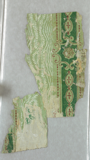 a and b are joined together. a): Outlines (incomplete) of a possible medallion, and pin dots, in green. Traces of white scroll work; b): A vertical stripe of dark green set with medallions to one side of which are white wavy grasses. Additional fragment adheres to this; c): Red and green ladder design.
