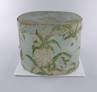 "Wooden bandbox covered in wallpaper with pineapple pattern. Coloring of exposed areas much faded, better preserved paper sample with vivid coloring around rim. Turquoise-green background (light blue in exposed areas) with background fill of deep pink dots (white in exposed areas), white trailing leaves and flowers, bold repeating pattern of cluster of three pineapples in white and pinks with green leaves. Lined with newsprint: ""Christian Panoply"". Paper label inside lid: ""Warranted/ Nailed/ Bandboxes/ Made by/ Hannah Davis""."