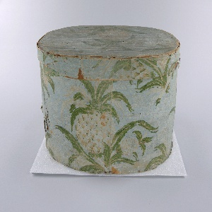 """Wooden bandbox covered in wallpaper with pineapple pattern. Coloring of exposed areas much faded, better preserved paper sample with vivid coloring around rim. Turquoise-green background (light blue in exposed areas) with background fill of deep pink dots (white in exposed areas), white trailing leaves and flowers, bold repeating pattern of cluster of three pineapples in white and pinks with green leaves. Lined with newsprint: """"Christian Panoply"""". Paper label inside lid: """"Warranted/ Nailed/ Bandboxes/ Made by/ Hannah Davis""""."""
