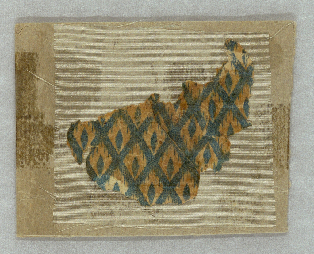 Very small fragment: small diaper or diamond trellis pattern with single diamond in each grid. Printed in deep blue on ungrounded paper or tan ground. Sample is mounted on a small cardboard support.
