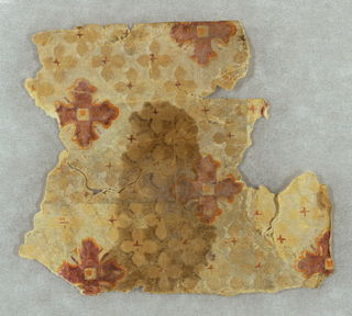 Red quatrefoil motif, outlined in orange, set within diaper framework composed of smaller tan quatrefoil motifs.