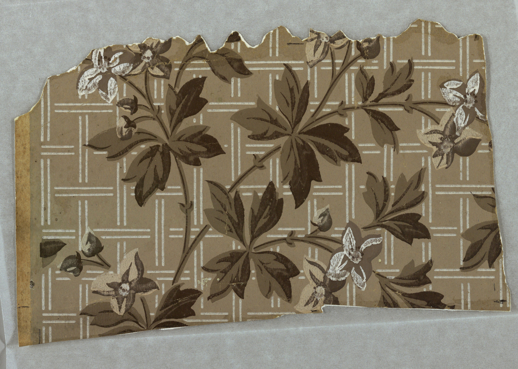 Portion of a paper showing a pattern of vines and flowers against a field divided into squares by paired white lines. Printed in white and grays on gray ground.