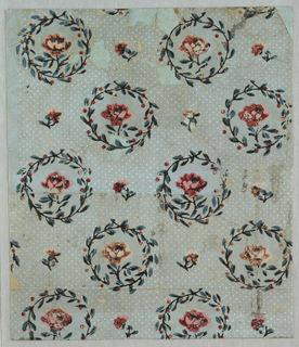 Diagonal lines of white dots on a pale blue field. Dotting interrupted by repeating wreath medallions containing roses, with rose buds sewn over field. Vertical rectangle.
