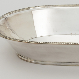 Oblong, with high flared sides; reeded band covers narrow base; silver die-stamped edge with egg and dart motif applied to rim.
