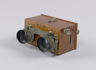 Small stereoscope, with box that opens to show metal rack that holds the slides. Knobs at side to adjust focus. Manufacturer's name on metal inside case.