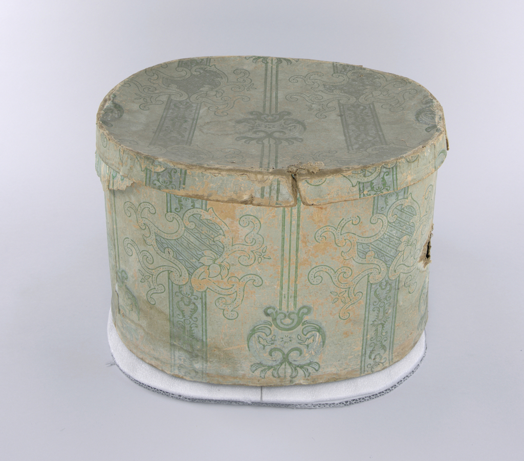 On light blue ground, slightly deeper blue bandings, vertical, with green pattern of: vertical lines, scrolls and leafy patterns. Over the vertical blue bandings, green pattern with leaves between paired bordering lines giving ribbon-like effect, interrupted by assymetrical lambrequin-like shape of scrolls and flowers with diagonal linear fill and pin-work. Paper covers sized coton reinforcement which is visible at worn edges.