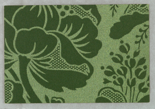 Green paper, embossed with shiny surface to imitate damask. Part of what appears to be a large floral design is shown.