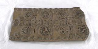 Rectangular block consisting of three layers of wood, of which the upper is carved. Two pairs of large and two pairs of smaller wreaths centering leaves. Double row of small trefoils and dots, in brass, through center, and single row at top and bottom.